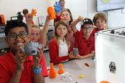 School children with 3D printed parts they produced
